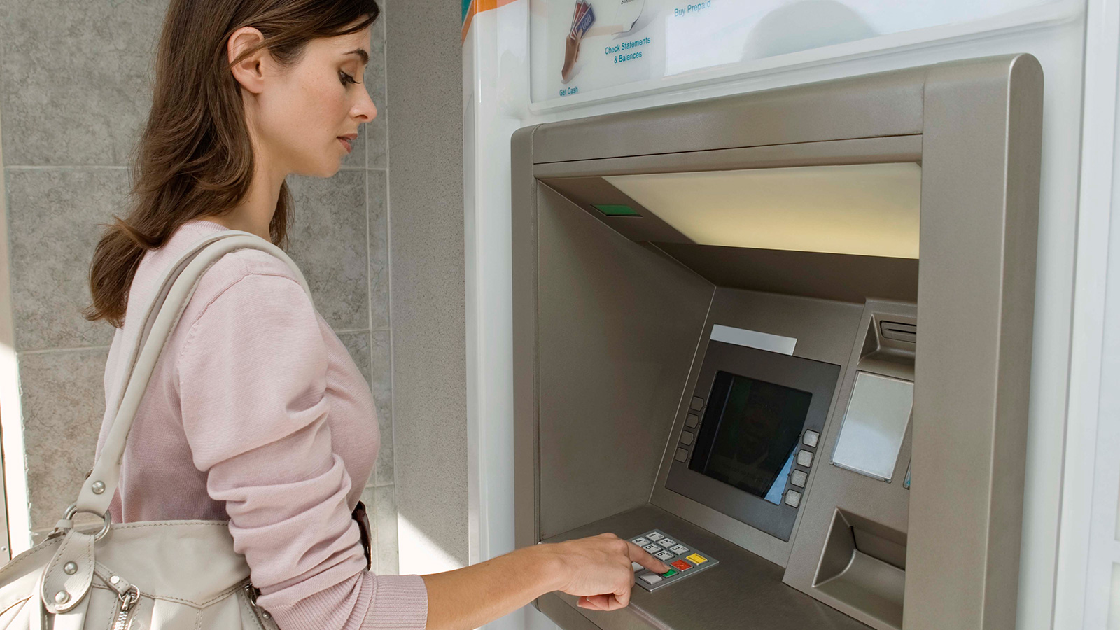 Woman using ATM.