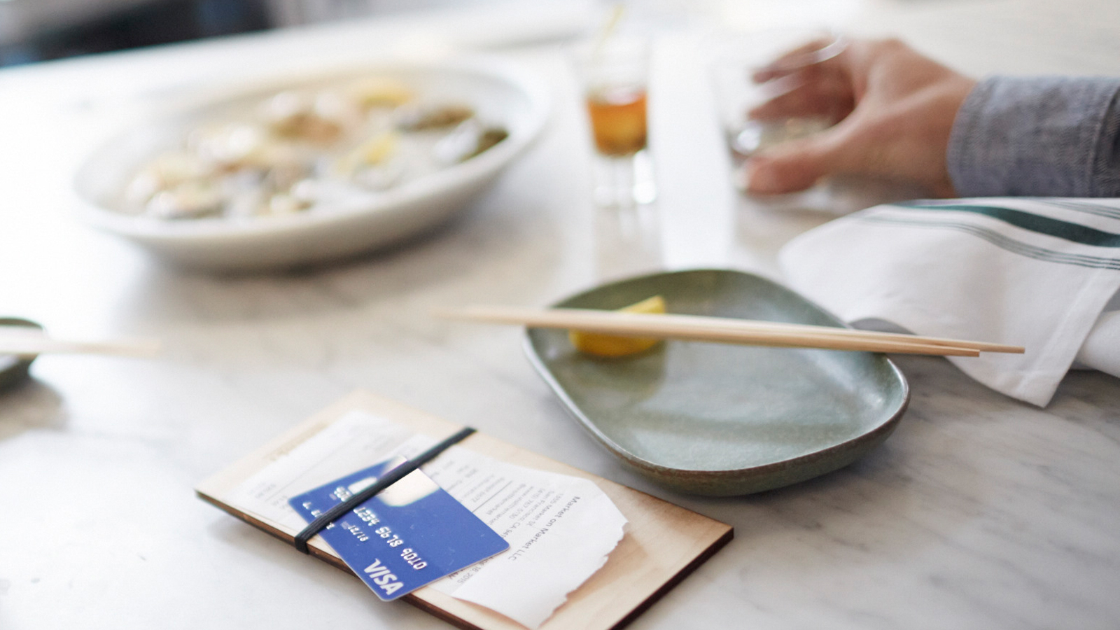 A restaurant table with plates of food and drinks showing a Visa card on top of a check.